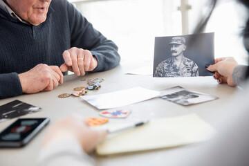 Senior man showing old photographs and memorabilia