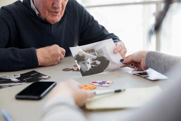 Senior man showing old photographs to woman