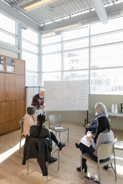Senior man leading support group at whiteboard in community center