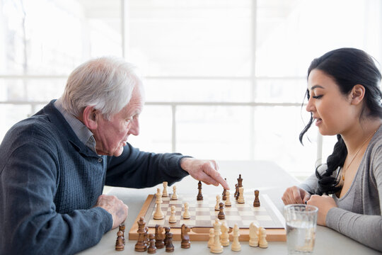 Senior man playing chess with young woman in community center