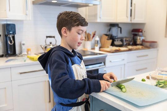 Boy chopping cucumber in kitchen