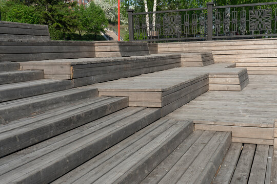 A multi-tiered wooden amphitheater near the riverbank.