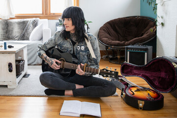 Young transgender woman playing guitar on floor
