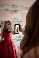 Teenage girl in prom dress video chatting with friends on smart phone