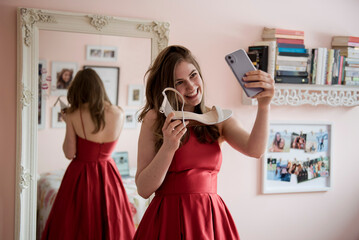 Happy teenage girl in prom dress showing shoes to friends video chat