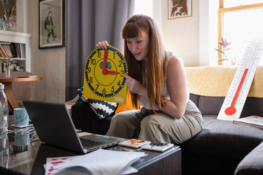 Female teacher with clock teaching at laptop on living room sofa