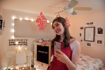 Happy teenage girl taking selfie with graduation sign in bedroom