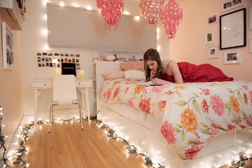 Teenage girl journaling on bed surrounded by string lights