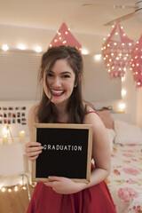 Portrait of smiling teenage girl holding graduation sign in bedroom