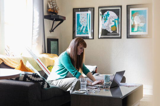 Female teacher working from home at laptop in living room