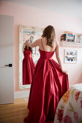 Teenage girl in red prom dress video chatting with friends