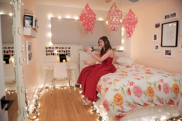 Teenage girl in red dress video chatting in bedroom