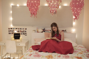 Teenage girl in red dress journaling on bed