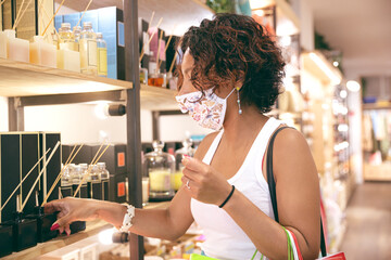 A woman wearing a mask looking at products inside a store in a shopping center. Selective focus. Concept of safe shopping and social distancing.