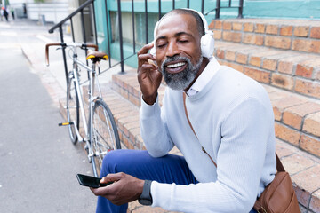 African American man sitting on stairs and using his phone