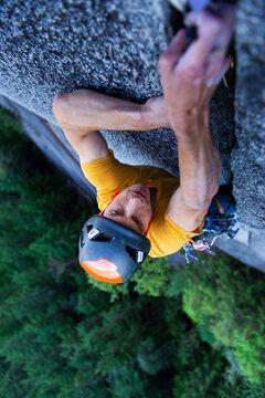 Man placing big cam in granite off-width crack lead climbing Squamish