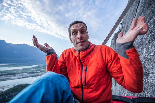 Man with surprised look showing interrogation on portaledge at sunset