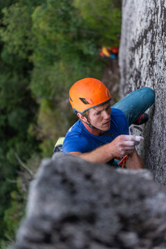 Close-up of man lead climbing and placing gear with helmet and focus