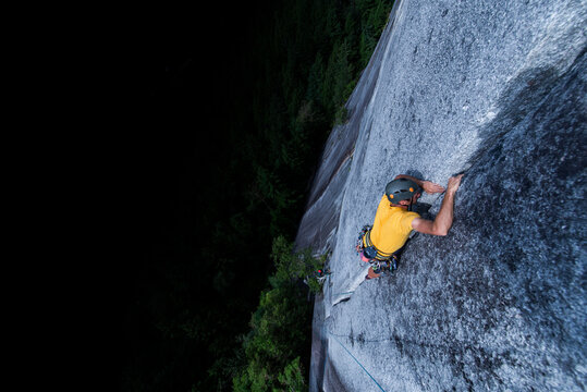 Man lead climbing granite crack very high and exposed Squamish chief