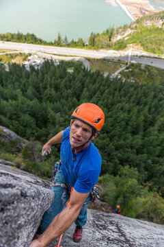 Man lead climbing a multipitch climb looking concerned about next move