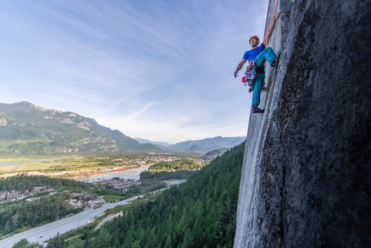 Man lead climbing granite Squamish with background view of valley