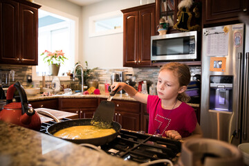Candid Image of Unsmiling Young Girl Cooking Eggs In Messy Kitchen