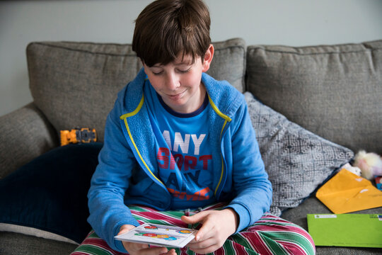 Smirking Teen Boy Reads Birthday Card While Sitting on Couch in Pjs