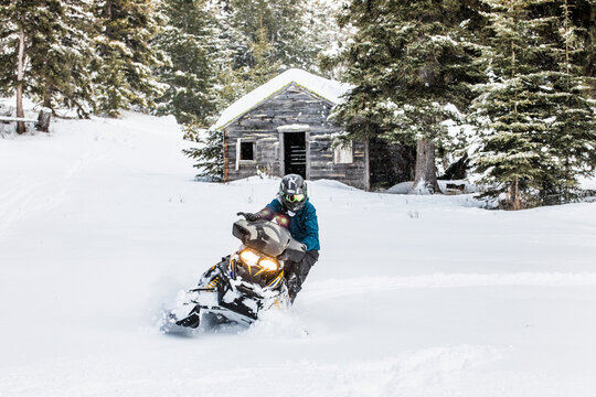 confident man on snowmobile with old cabin behind.