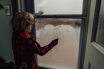 Little boy drawing a picture on the window condensation