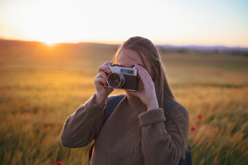 girl taking a picture in the field with old camera