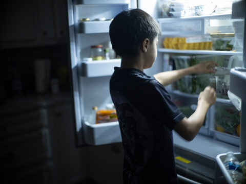 A 12 year-old boy searches in fridge for late night snack
