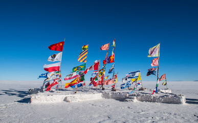 international flags planted on the salt flats of Uyuni in Bolivia