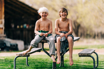 Two children smiling sitting on picnic table