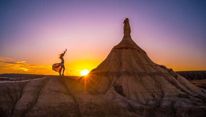Silhouette of a blonde girl in a long dress at the desert sunset