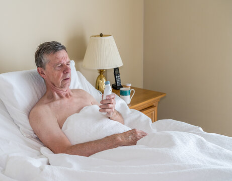Senior retired caucasian man lying in adjustable bed on incline. He is checking his temperature for fever or signs of virus