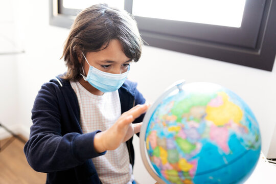 Young spanish boy holding a desk globe wearing a medical mask