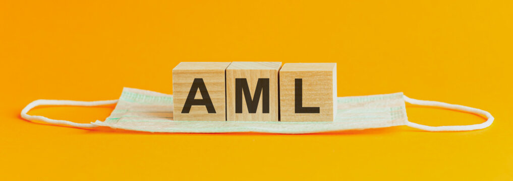 concept of the word AML on cubes on a wooden yellow background