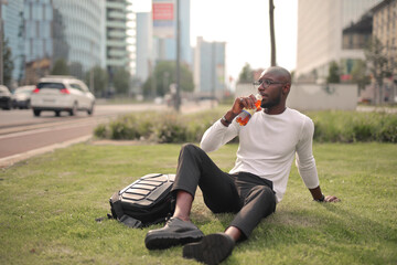 young man drinks from a bottle in a city park