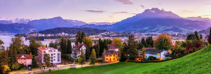 Photo sur Aluminium Lilas Skyline Panorama of Lucerne, Switzerland. Picturesque night view of illuminated European old city beneath dramatic sky during autumn season. Swiss cityscape from above.