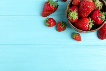 Fototapete - Delicious ripe strawberries in bowl on light blue wooden table, flat lay. Space for text