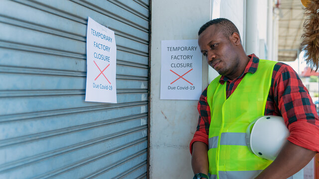 engineer with factory closed notice from coronavirus covid-19 pandemic