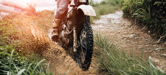 rider on a motorcycle rides a puddle of mud  splashing around