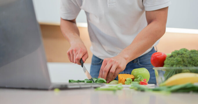close up man hand using knife to cut vegetables on board and preparing food while open laptop to practice from streaming website and cooking online course for healthy living concept