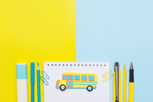 Colorful stationary school supplies on yellow and blue trending background and painted yellow bus in the center of note with a copy space