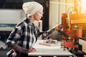 Female craftsman working at joiner machine