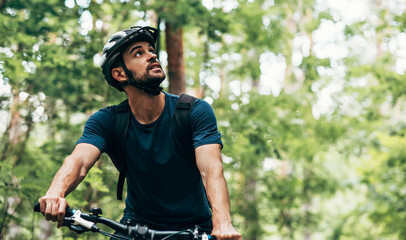 Outdoor image of handsome cyclist man riding bike in the mountain. Male athlete in cycling gear practising outside in the forest on nature background. Travel and extreme sport concept.