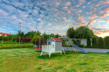 Garden playground for children with lovely little house at sunset