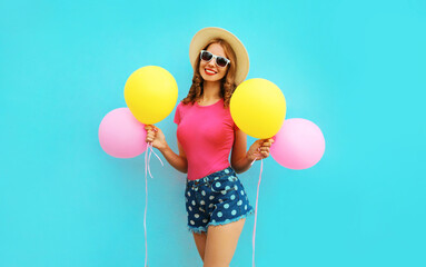 Summer colorful cheerful image of happy smiling young woman with yellow pink balloons having fun wearing a shorts and straw hat on blue wall background