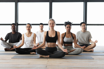 Multi-cultural group of young people sitting in lotus position, meditating together