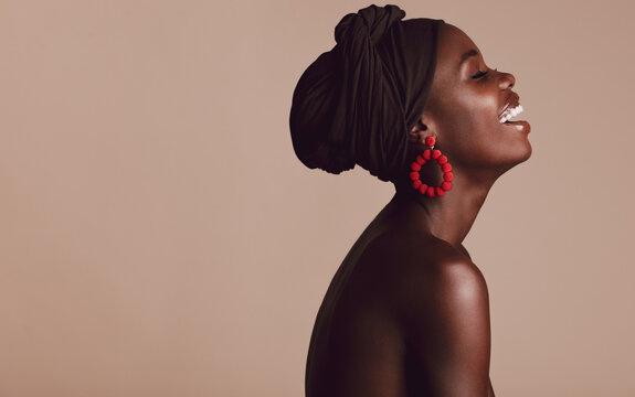 Fashionable african woman smiling on beige background
